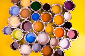 Open buckets with a paint, yellow background