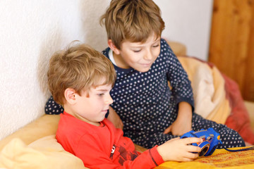 Two preschool or school kids boys, siblings and brothers having fun after school day playing video game at home and taking pictures with toy camera. Best friends, twins in pajamas or nightwear