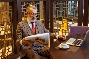 Portrait of mature wealthy man in years having coffee break at his private cabinet, home parlor, reading business article in newspaper and following to the latest news in laptop screen