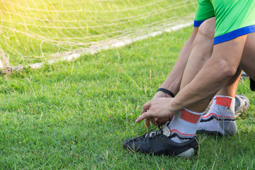 Young asian athlete man tying football shoes beside the field,male football ready for play on the field,wellness and sport concepts