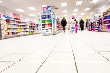 Abstract background blurred photograph of an aisle with shelves in bright modern drugstore at supermarket shopping center