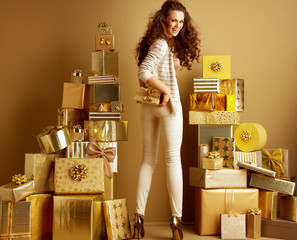 smiling trendy woman holding present box in front of plain wall