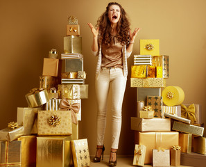 woman among 2 piles of golden gifts in front of plain wall