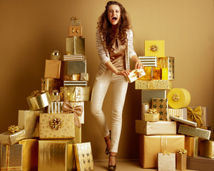 happy fashion-monger with gift box in front of a plain wall