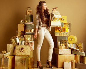 smiling woman with gold shopping bags speaking at smartphone