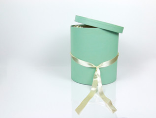 Decorative Round Teal Hat Box with Cream colored ribbon isolated on plain white background