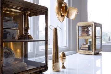 Dekoration in Gold und Messing auf weissem Tisch vor Fenster in heller Altbauwohnung