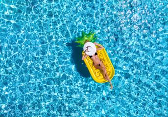 Junge Frau im Bikini mit Sonnenhut entspannt auf einer Luftmatratze in Ananasform auf blauem, erfrischendem Wasser