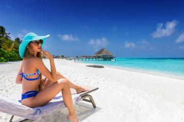 Attraktive, junge Frau im Bikini genießt ihren Urlaub auf einer Liege am tropischen Strand der Malediven