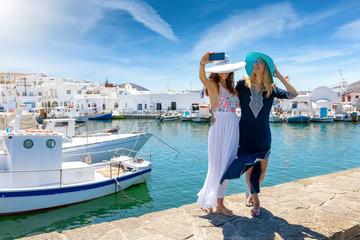 Zwei attraktive, reisende Freundinnnen machen ein Selfie Foto am Hafen des Fischerortes von Naousa, Kykladen, Griechenland