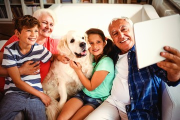 Grandparents and grandchildren taking a selfie with digital