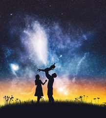 Happy parents with a baby on night sky.
