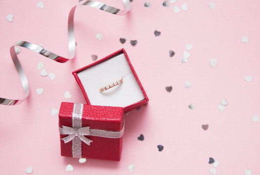 Red gift box with a jewelry on festive background.
