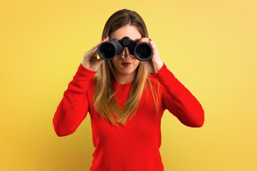 Young blonde woman with binoculars on yellow background