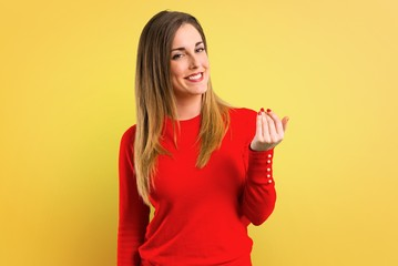 Young blonde woman presenting and inviting to come on yellow background