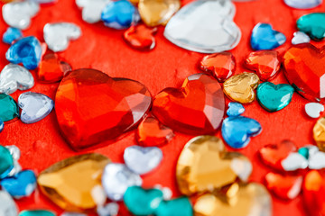 Multicolored glass hearts on a red background. The concept is suitable for love story and for Valentine's Day