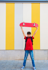 Happy youngster with skateboard above head