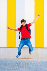 Cheerful young boy jumping against multicolored wall on a sunny day