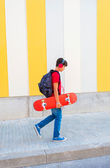 Side view of a young boy wearing casual clothes walking against a colored wall while holding a skateboard