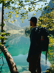 Backpacker looking at lake while standing by branches in forest