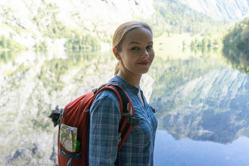 Portrait of smiling female backpacker standing by lake against mountains in forest