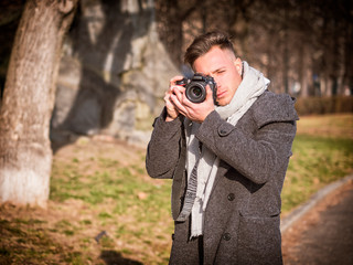 Handsome young male photographer taking photograph with professional photo camera, outdoor in city park