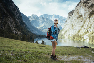Full length of female backpacker looking at view by lake and mountains in forest