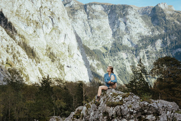 Full length of female tourist looking at mountains while sitting on rock in forest