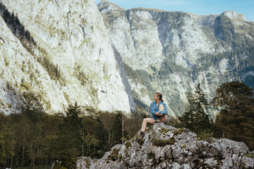 Female tourist looking at mountains while sitting on rock in forest