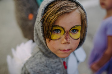 Cute boy with face paint wearing costume looking away during Halloween party