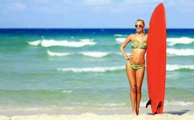 Full length portrait of fit woman with surfboard on a beach