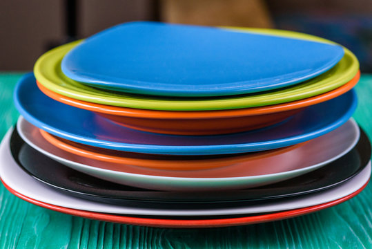 A stack of colored plates on a green wooden background.