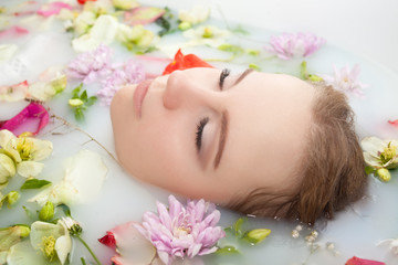 Spa beauty girl bathing in milk bath, spa and skin care concept. Beauty young Woman with perfect slim body and soft skin, in flower wreath relaxing in milk bath. Rejuvenation.