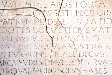Latin inscriptions background wallpaper on an ancient cracked marble slab in Rome. Wall mural