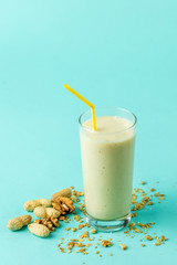 Spoed Foto op Canvas tasty milkshake in glass with straw. isolated blue background. health and body care