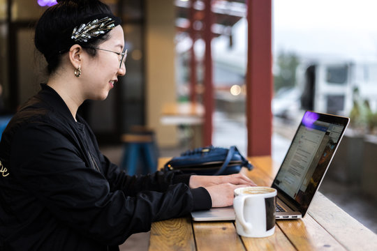 Smiling young woman working on laptop in cafe