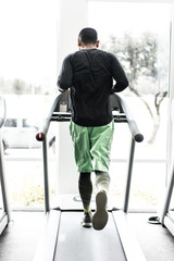 Rear view of man exercising on treadmill in gym