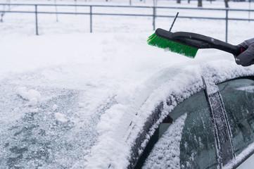 Зима. маленький мальчик чистит щеткой крышу автомобиля