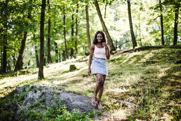 Smiling young woman standing in forest