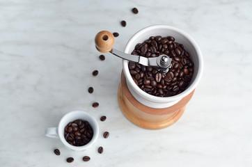 Macinino con tazzina e chicchi di caffè