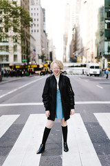 Portrait of woman standing on zebra crossing in city