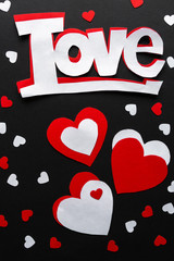 Valentines day. Paper hearts red and white on a black background. Holiday background with word love
