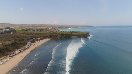 Aerial view rocky seashore with sandy beach. seascape ocean surf and tropical beach large waves turquoise water crushing on beach Bali,Indonesia. Travel concept.