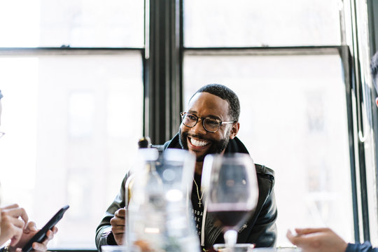 Smiling man sitting with friends in restaurant