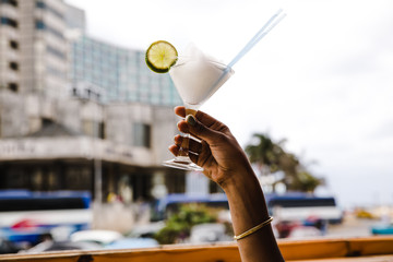 Woman's hand holding drink outdoors
