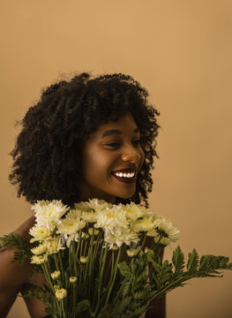 Smiling woman holding flowers while standing against beige background