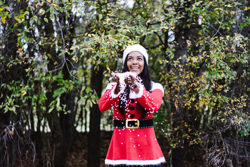 Woman in Santa suit costume playing with white confetti outdoors
