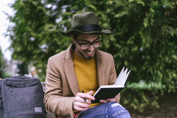 Smiling young man holding diary while sitting outdoors