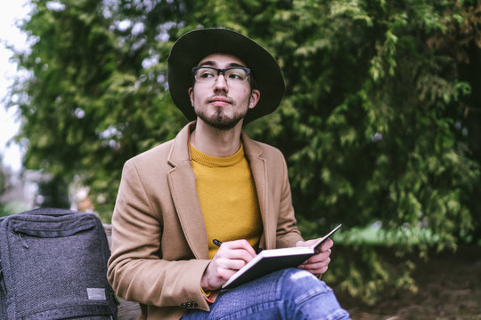 Young man writing in diary while sitting outdoors