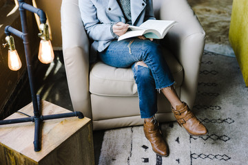Low section of woman reading book while sitting on armchair indoors